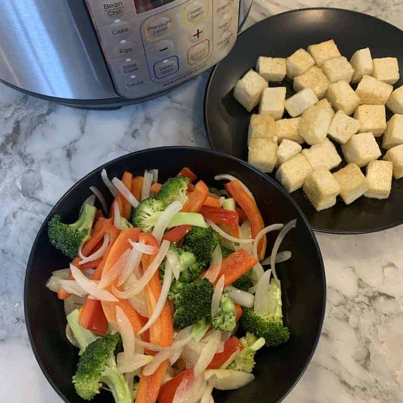 stir fried veggies in a balck bowl, tofu in a black plate with the Instant Pot in the background