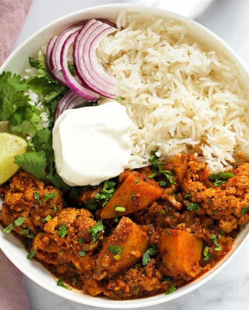 Cauliflower vindaloo curry served with rice, sliced onions and yogurt