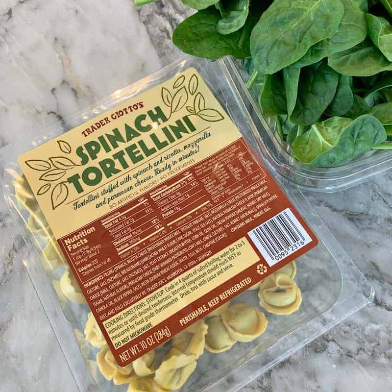 spinach tortellini and spinach on a cutting board