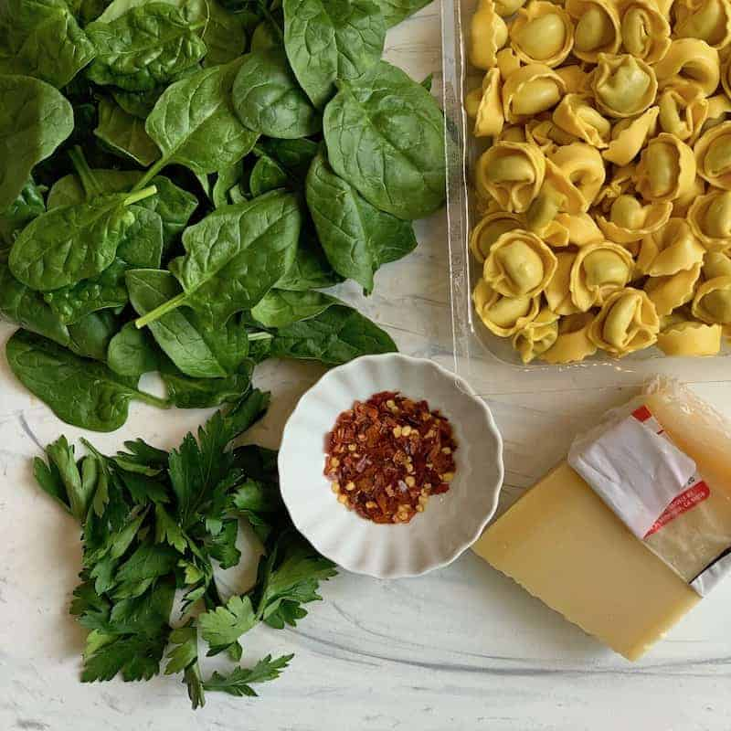 cheese, tortellini, spinach and parsley cutting board