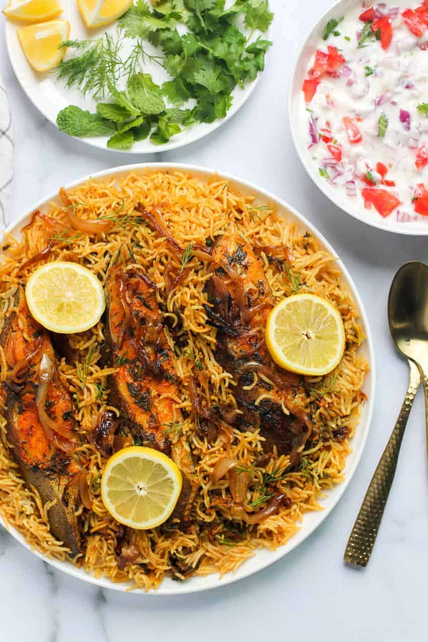 Fish Biryani with lemon slices and raita on the side