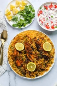Fish Biryani with Raita, lemon wedges and cilantro