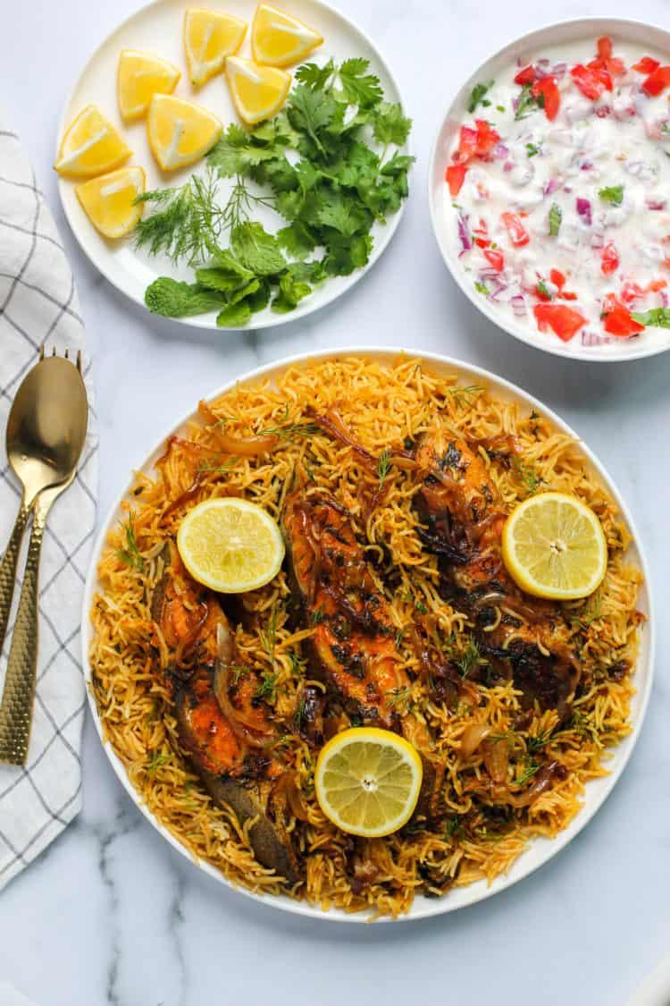 Fish Biryani with Raita, lemon wedges and cilantro