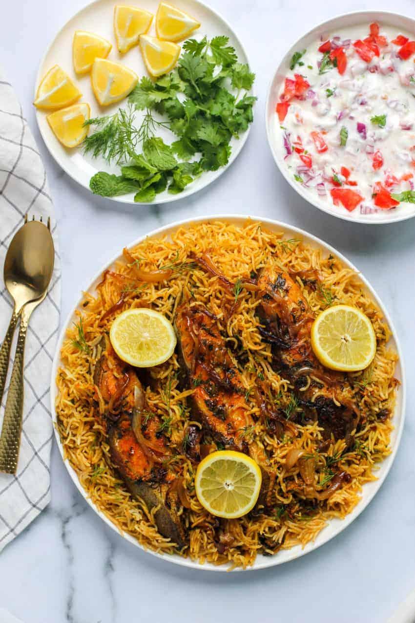Fish Biryani with lemon slices, raita and garnish on the side