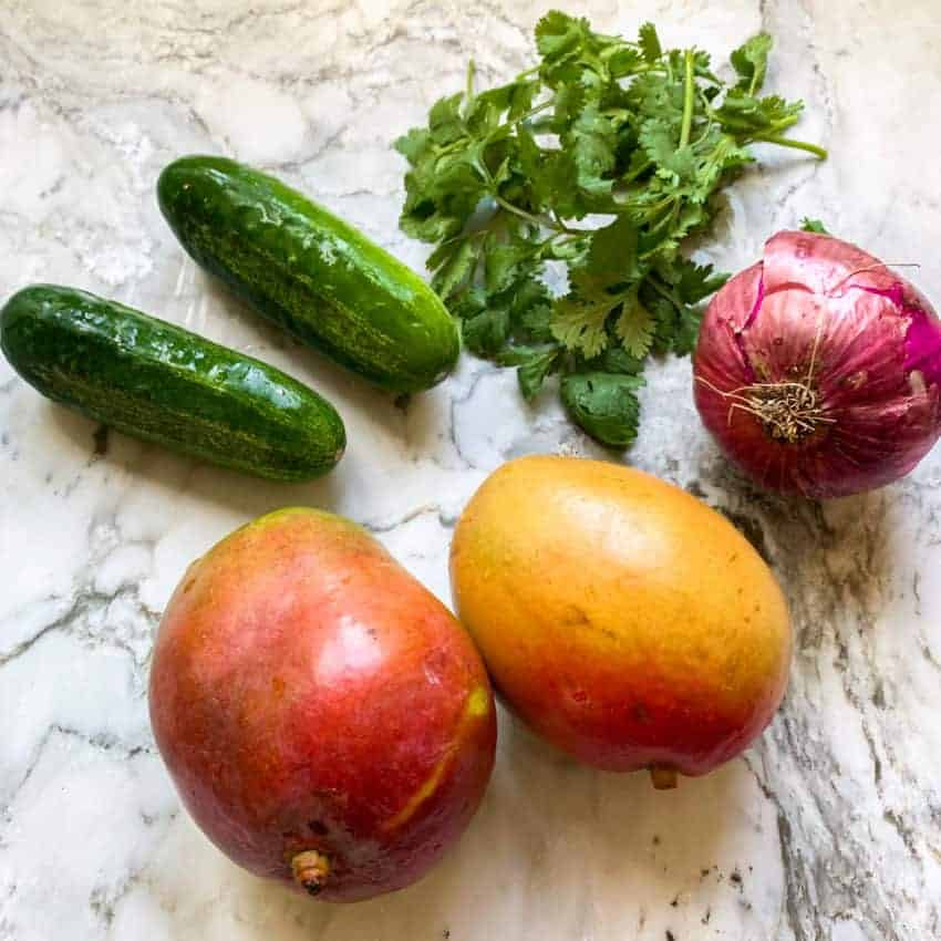 mangoes, cucumbers, red onion and cilantro on countertop