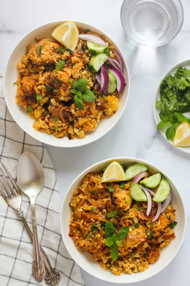 cauliflower rice chicken biryani in 2 white bowls