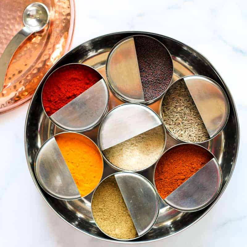 Spice box, masala dabba with individual bowls of whole and ground spices.