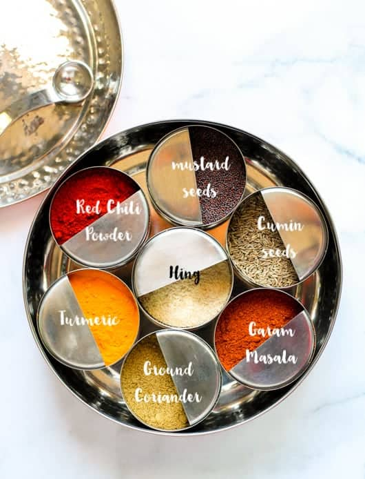 Indian Spice box, masala dabba with individual bowls of whole and ground spices.