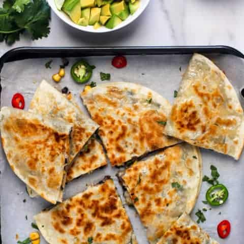 quesadillas on a tray with avocado and salsa on the side