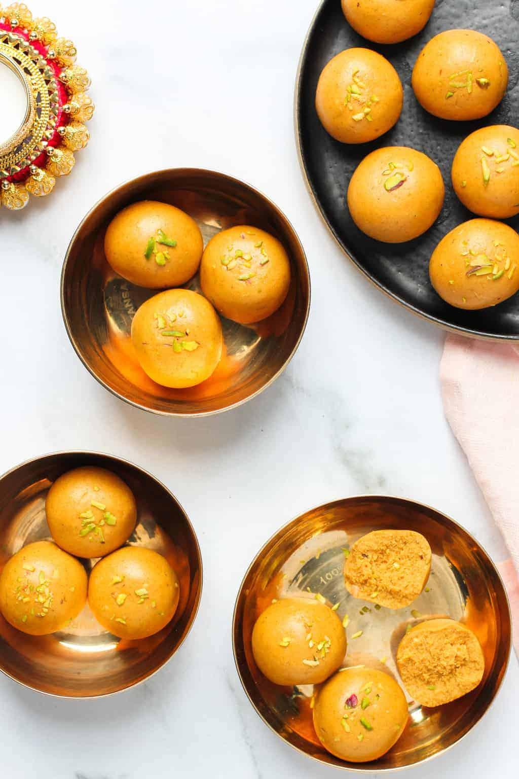 Besan laddu served in small brass plates
