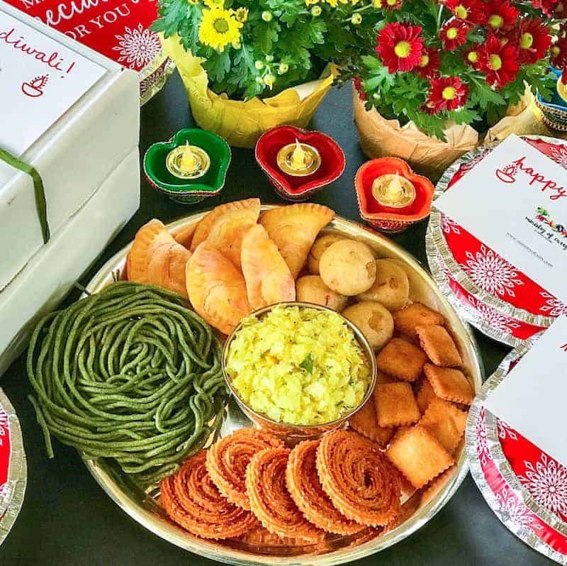 Diwali Sweets and Savories aka Faral in a platter with gift boxes on the side