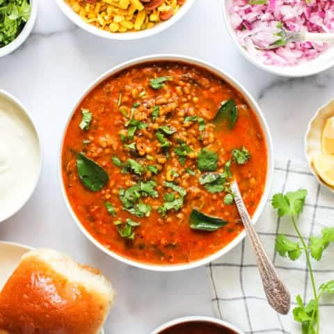 Misal Curry served in a big bowl with all the condiments on the side