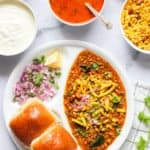 Misal Pav served in a white plate with all the garnish ingredients on the sides