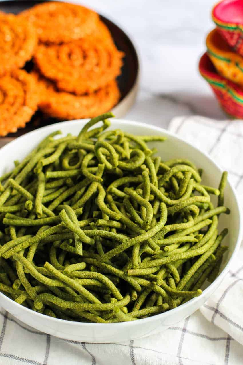 Spinach Sev in a white bowl with Chakli in the background