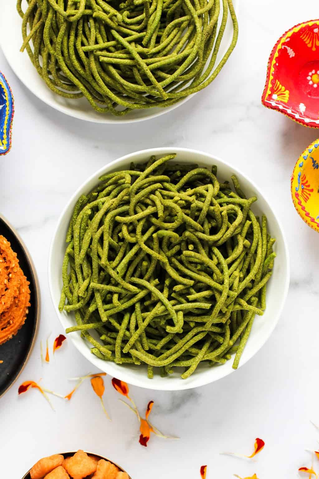 spinach sev in a bowl with other diwali snacks on the side
