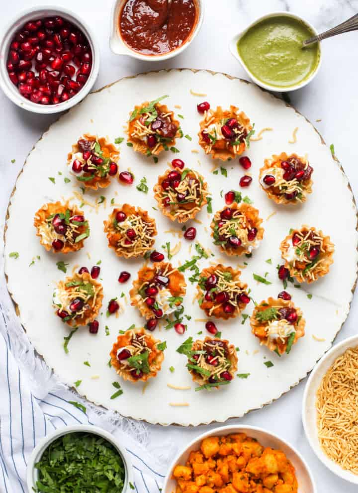 potato chaat served with garnish bowls on the side