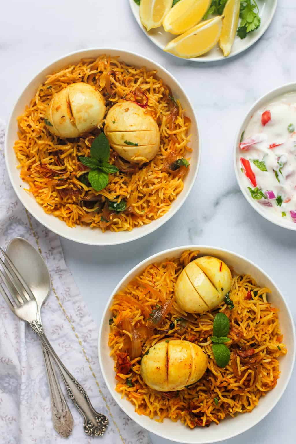 egg biryani served in 2 white bowls with raita and lemon