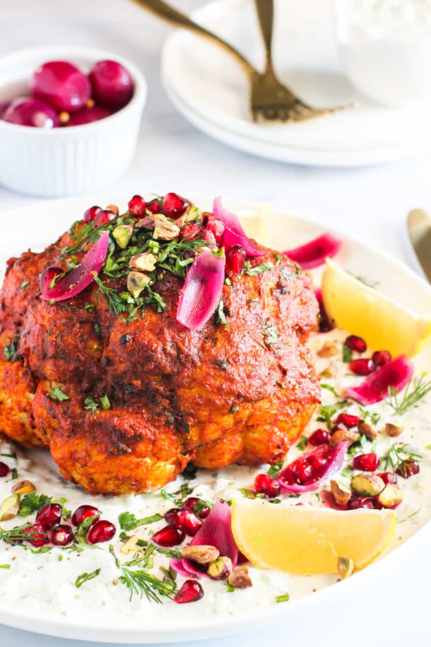 Whole rosted cauliflower garnished with pickled onions, pistachios & pomegranates.