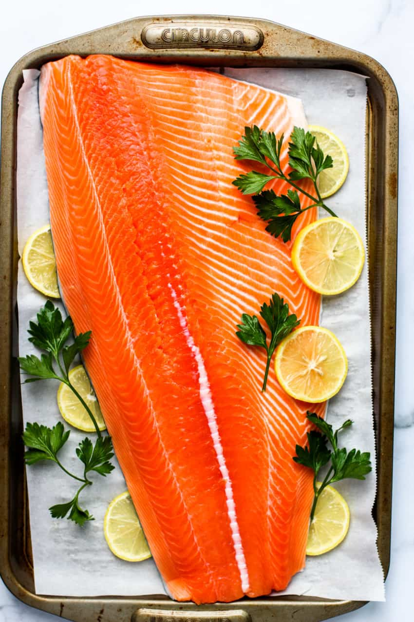 Raw salmon on a baking tray with lemon and parsley