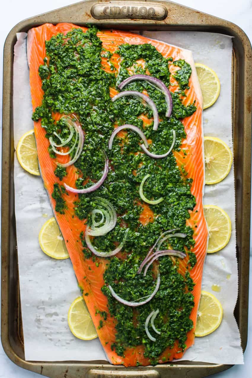 salmon coated with marinade and sliced red onion on a baking tray