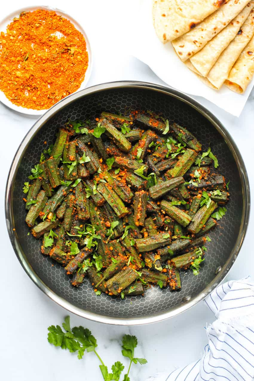 Stuffed okra in a frying pan with roti's on the side