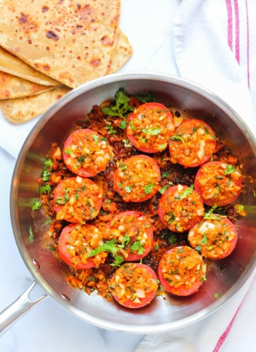 stuffed tomatoes in a frying pan with parathas on the side
