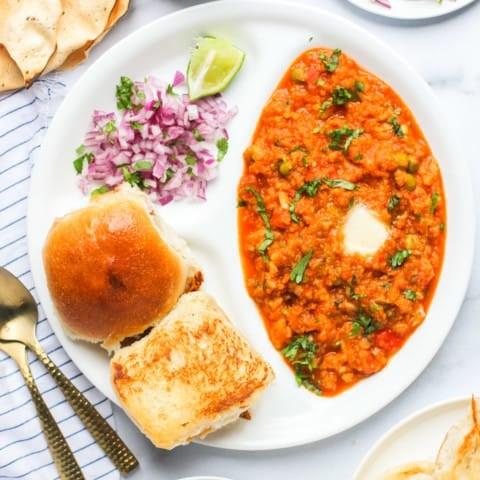 pav bhaji served with diced onions, pickle and papad