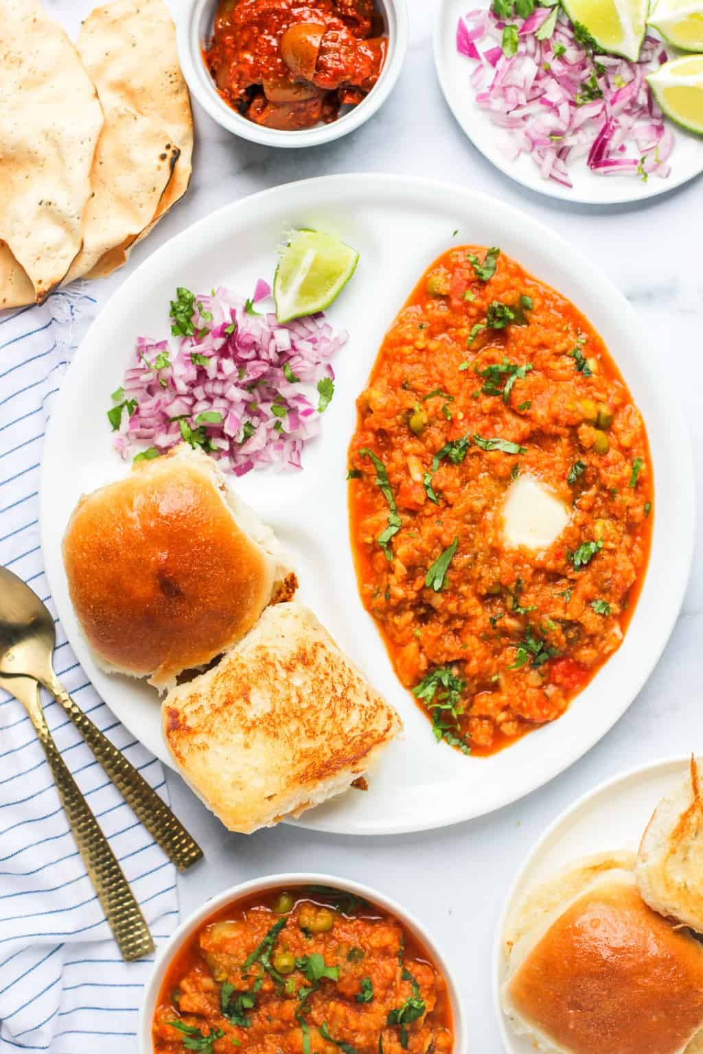 pav bhaji served with diced onions, pickle and papad