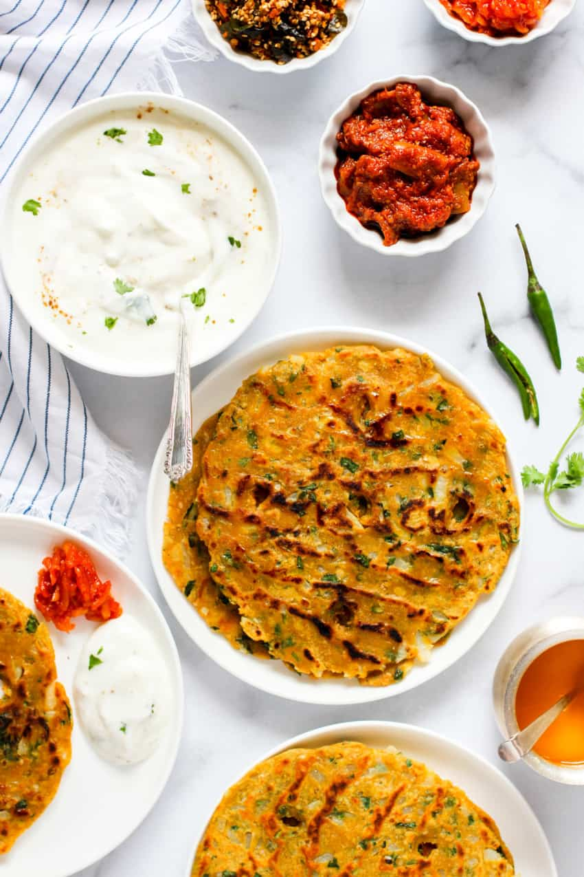 Thalipeeth served with side of pickle, chutney and yogurt