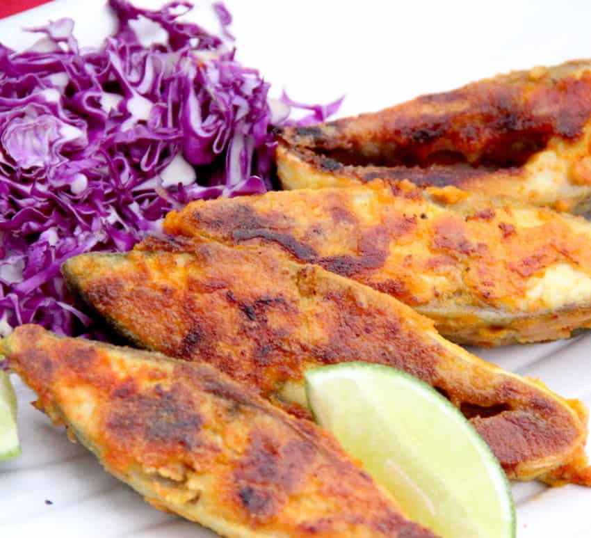 Pompano fish with lime wedge and shredded cabbage