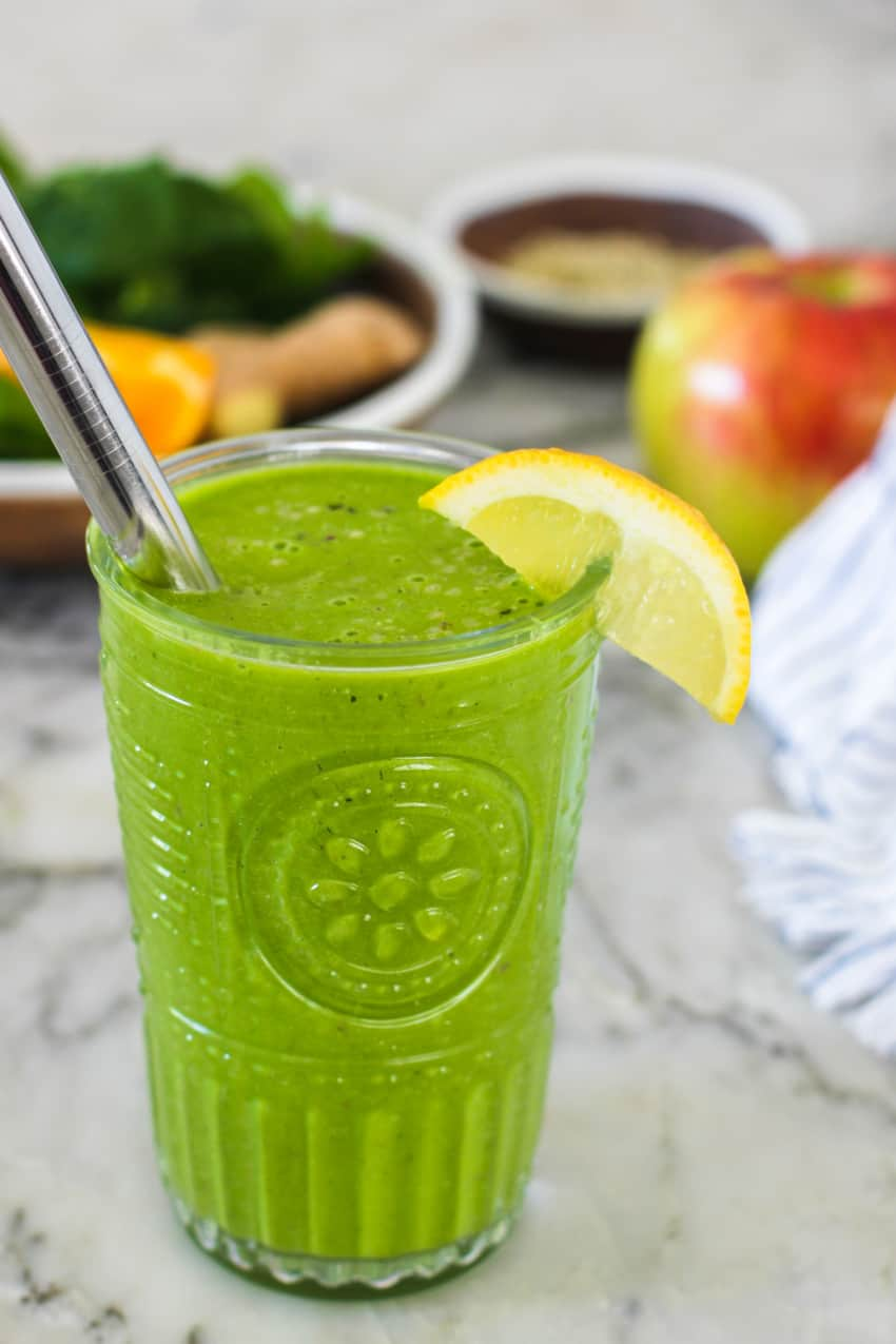 green smoothie in a glass with lemon wedge