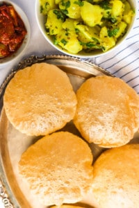 Puri in silver plate with potato bhaji and pickle