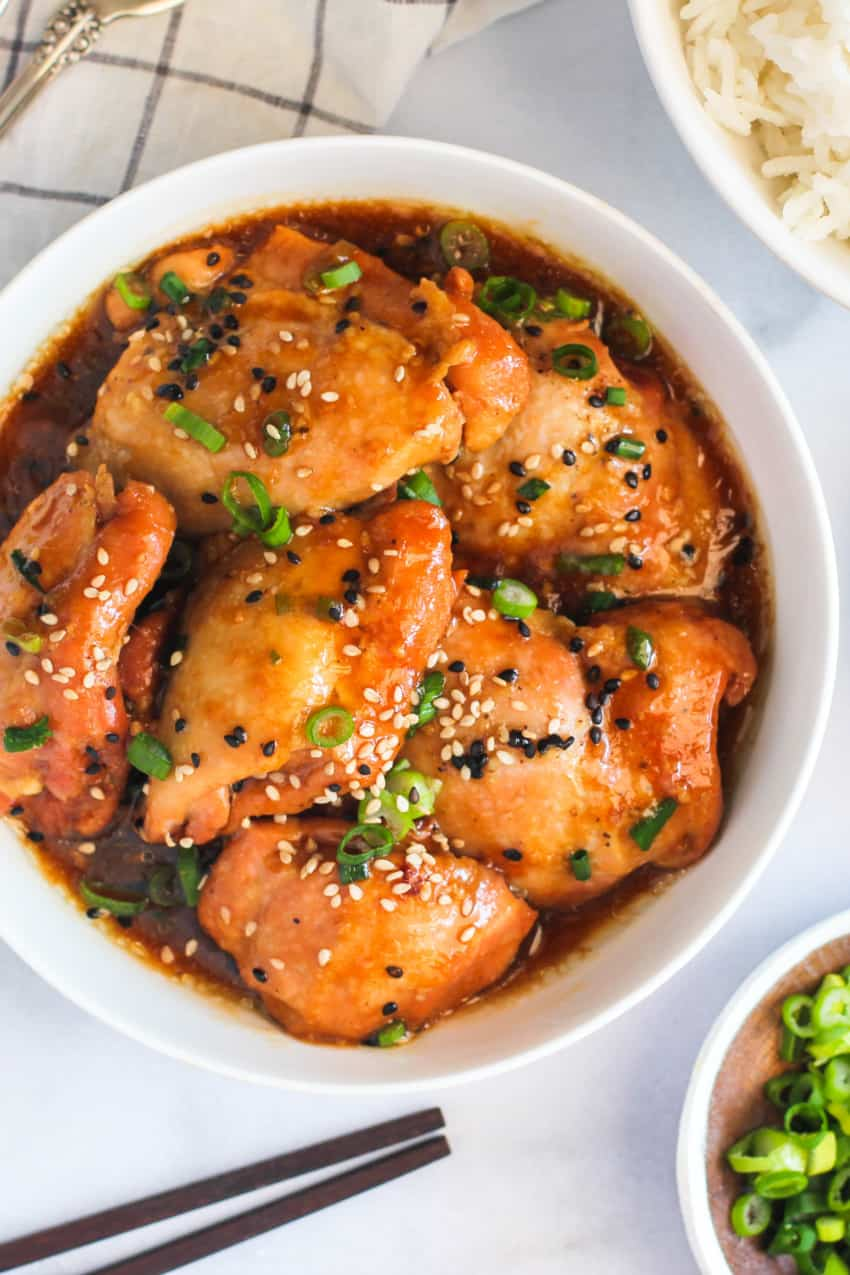 Chicken garnished with sesame seed and scallions served in a white bowl