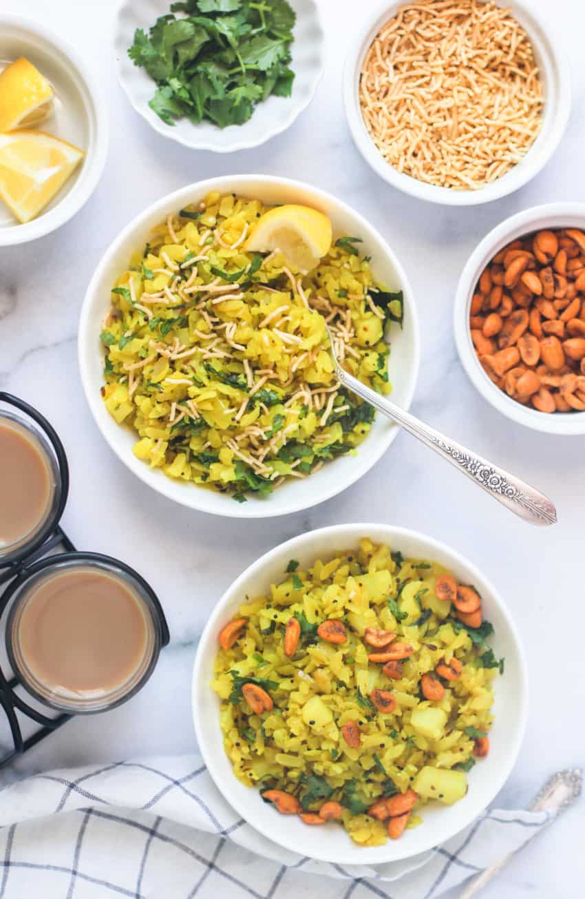 Poha served in white bowls with tea and toppings on the side