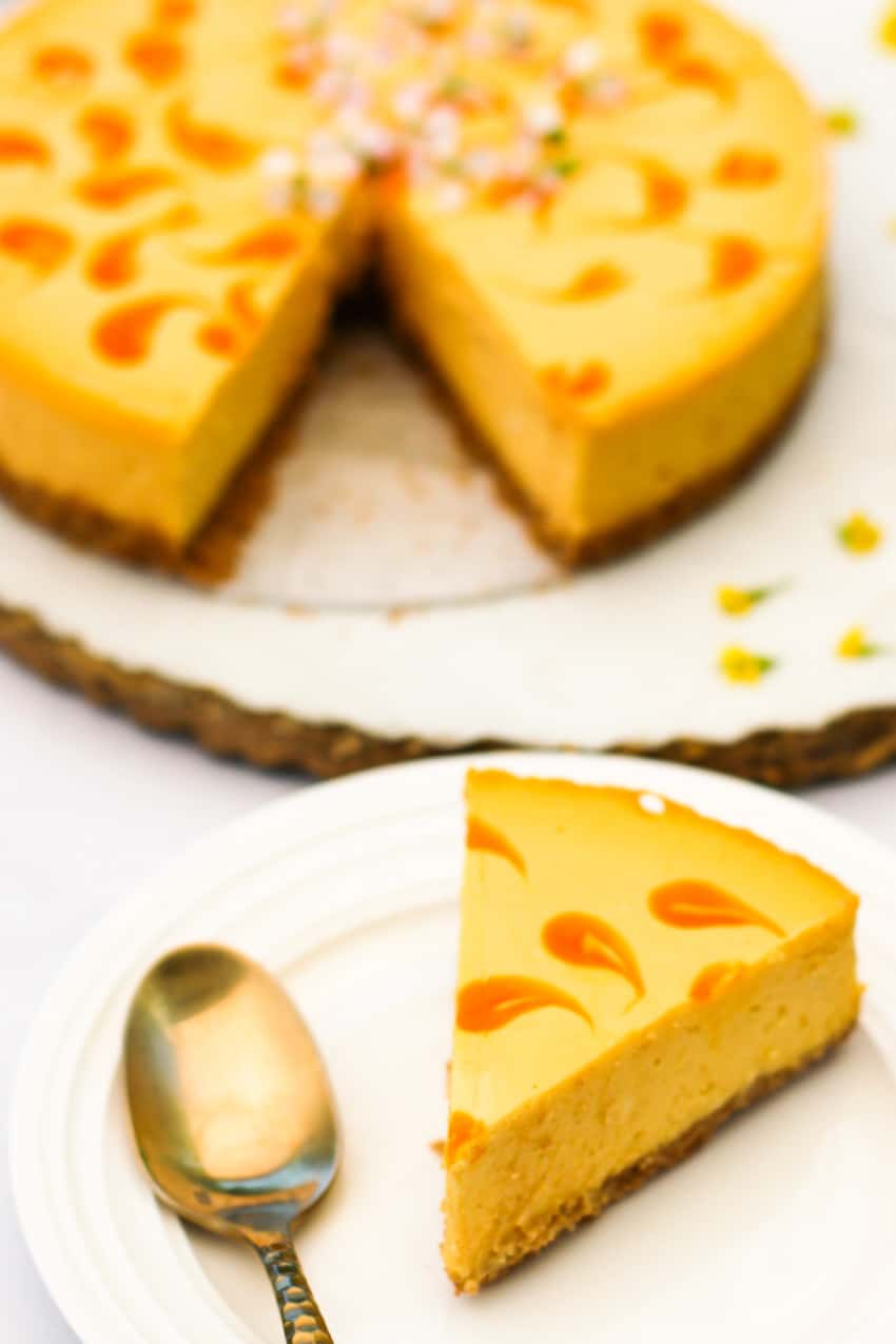 slice of mango cheese cake in a white plate with gold spoon