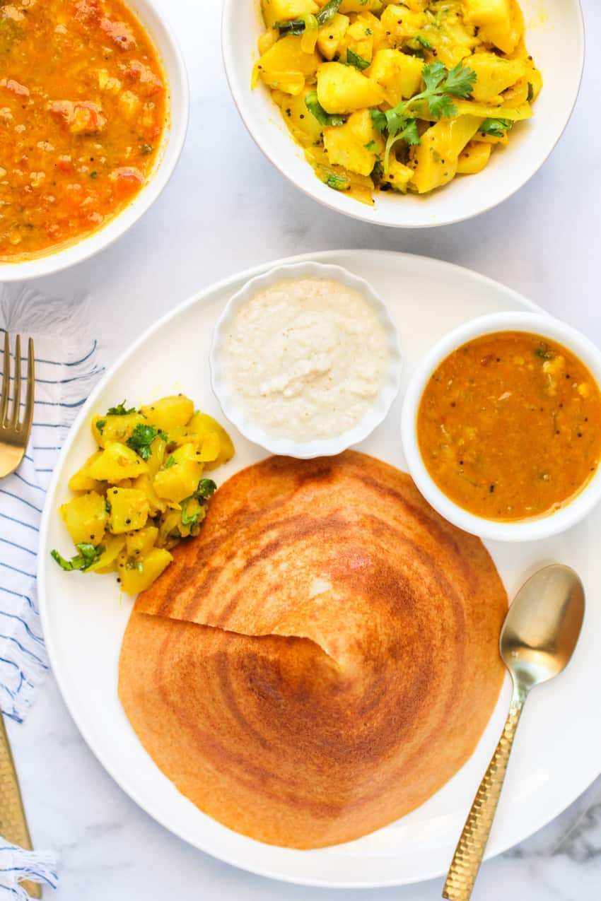 cone shaped quinoa dosa served with sambar, chutney & curried potatoes