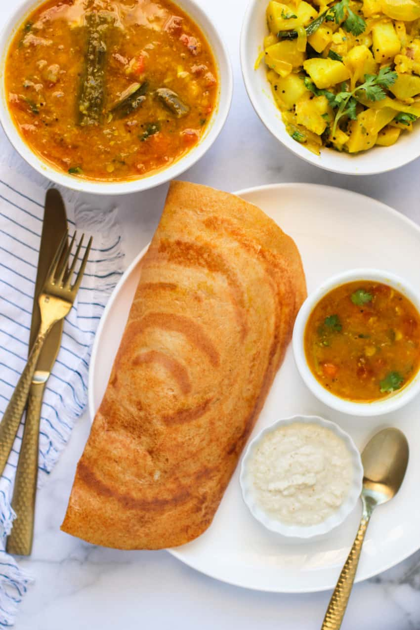 quinoa dosa served with sambar, chutney & curried potatoes