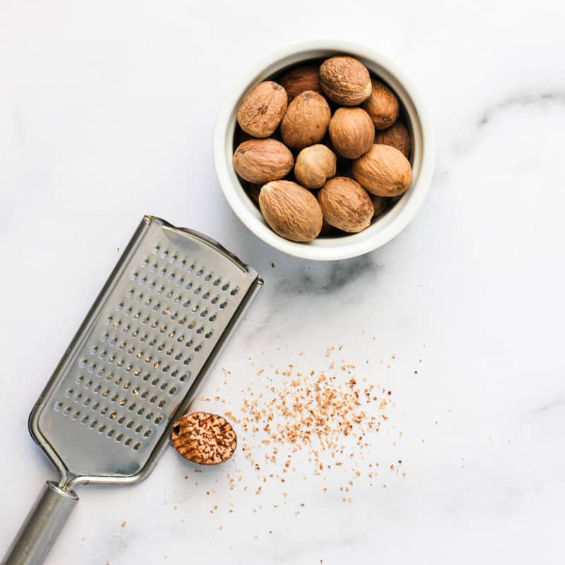 bowl with whole nutmeg and grater