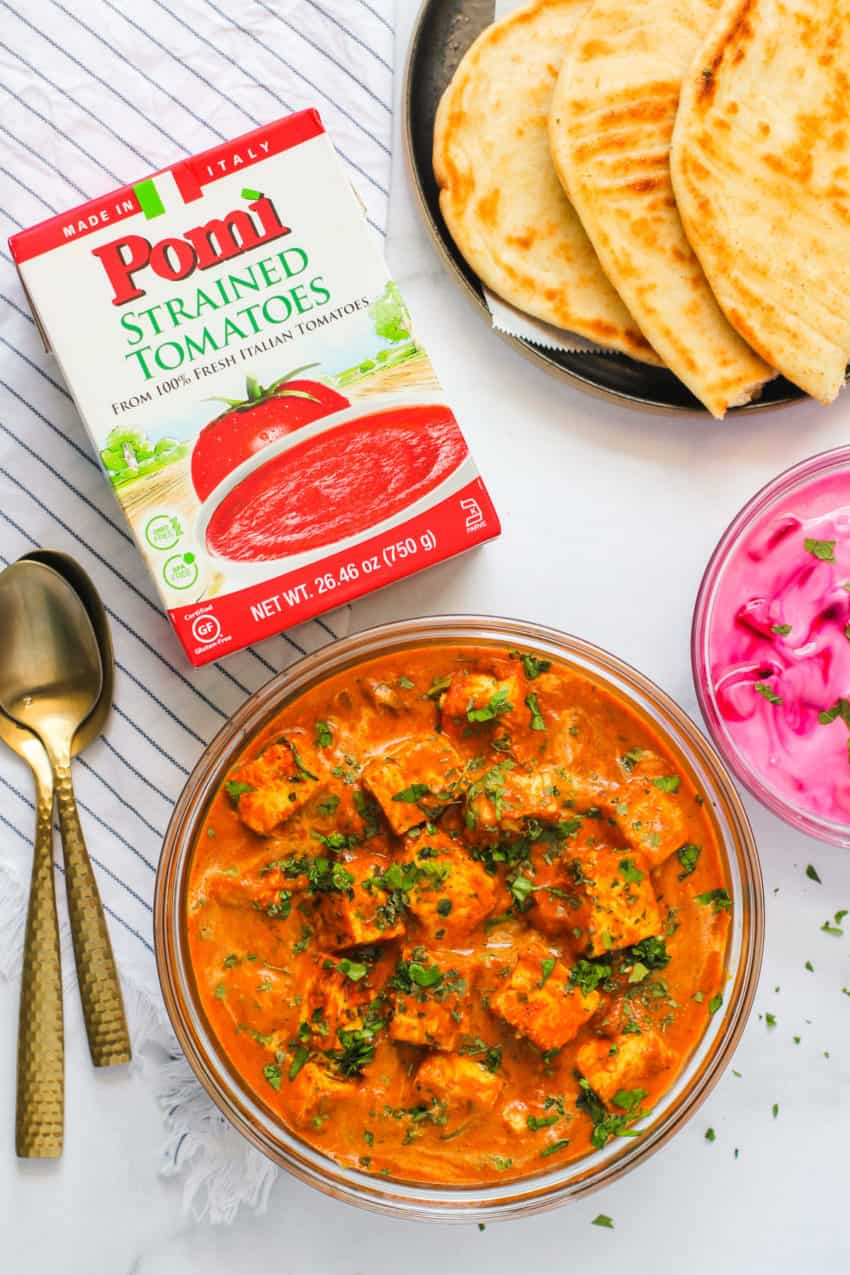 paneer butter masala with naan and raita with a box of tomatoes next.