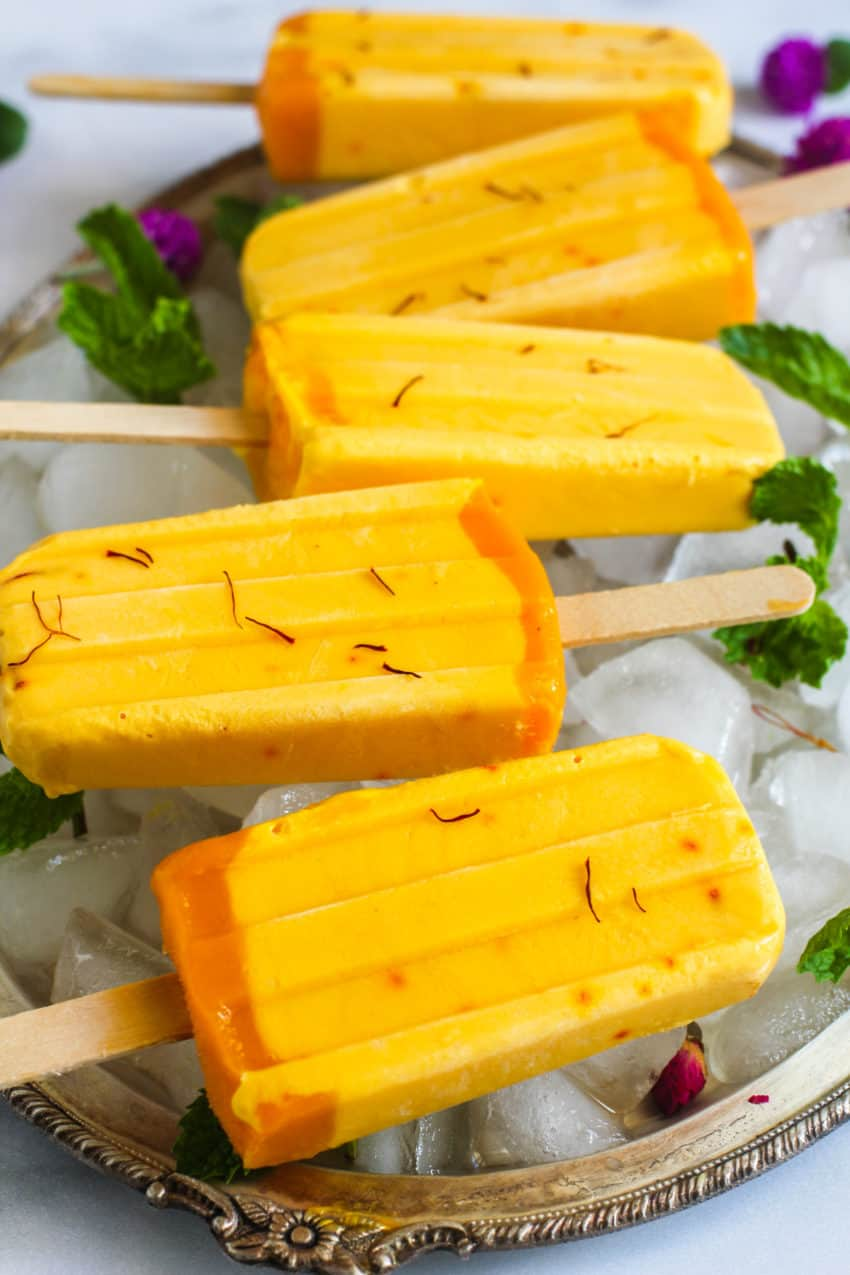 close up of a mango lassi popsicles on tray with ice