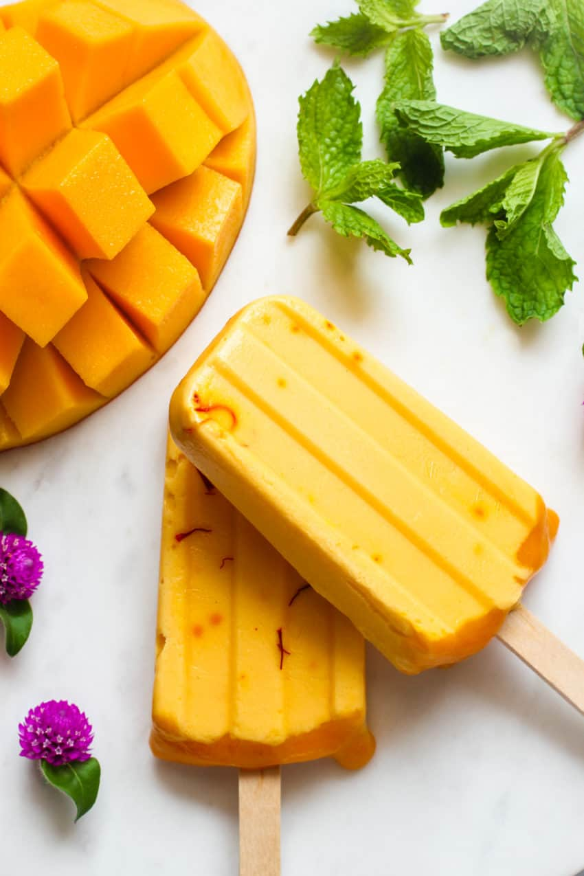 two popsicles stacked with cubed mango on the side