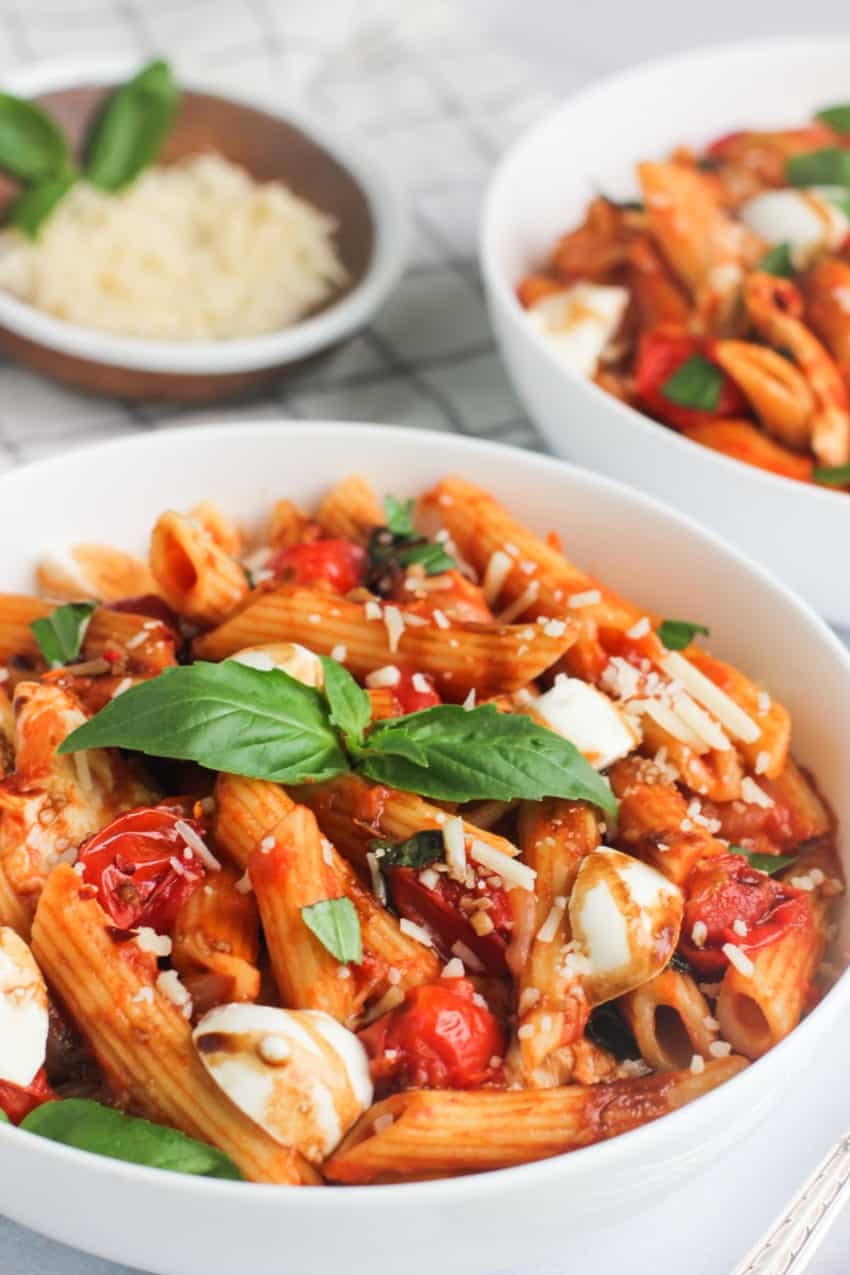 pasta caprese in white bowl with basil on top