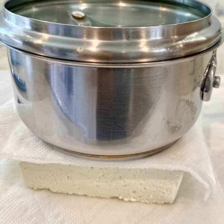 pressing tofu under a heavy pot