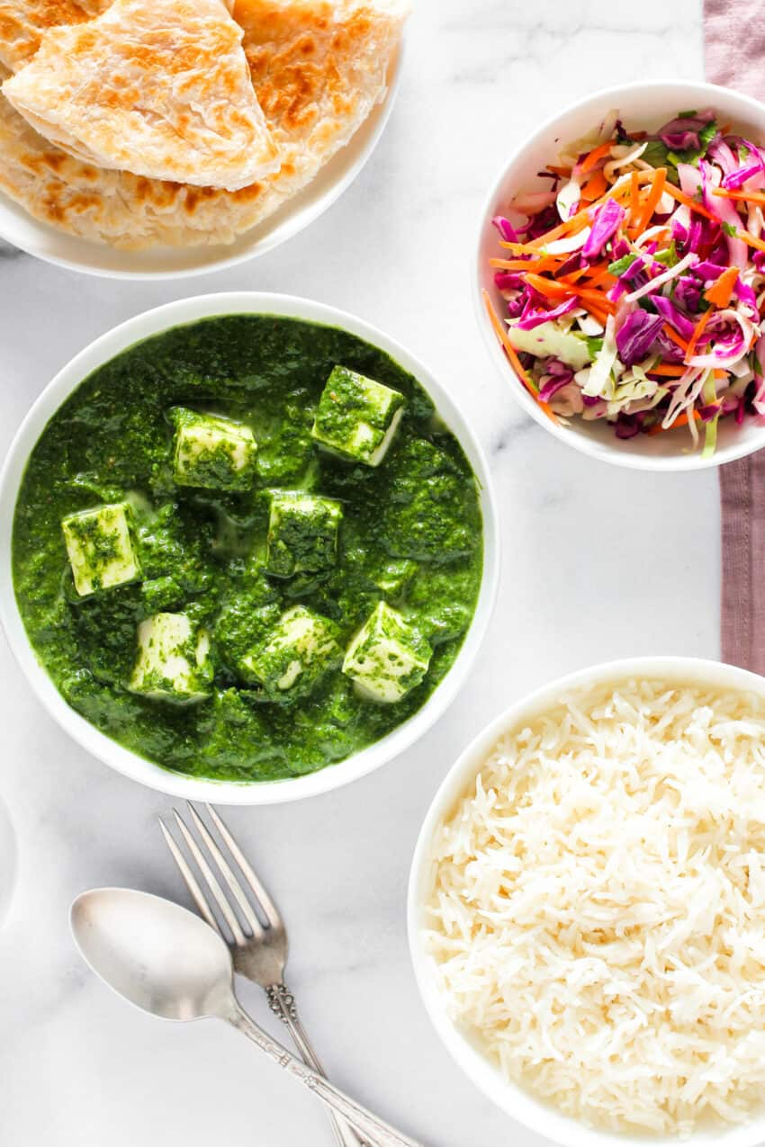 palak paneer served with parathas, rice and cabbage salad