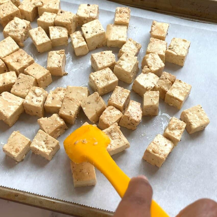 spreading tofu cubes on a baking tray
