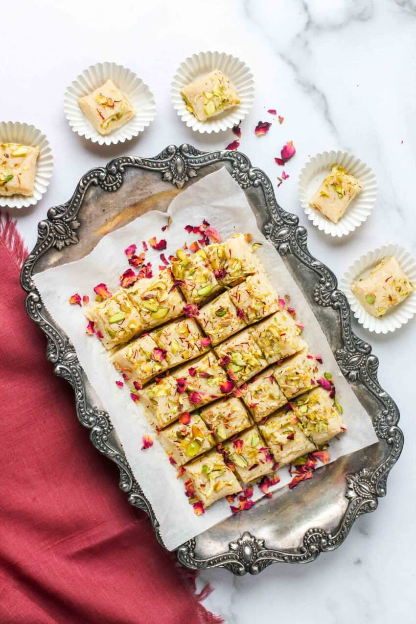 kalakand cubes in a silver platter and paper cupcake liners
