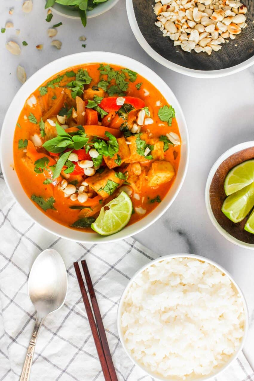 Thai Panang Curry garnished with basil and peanuts served in a white bowl