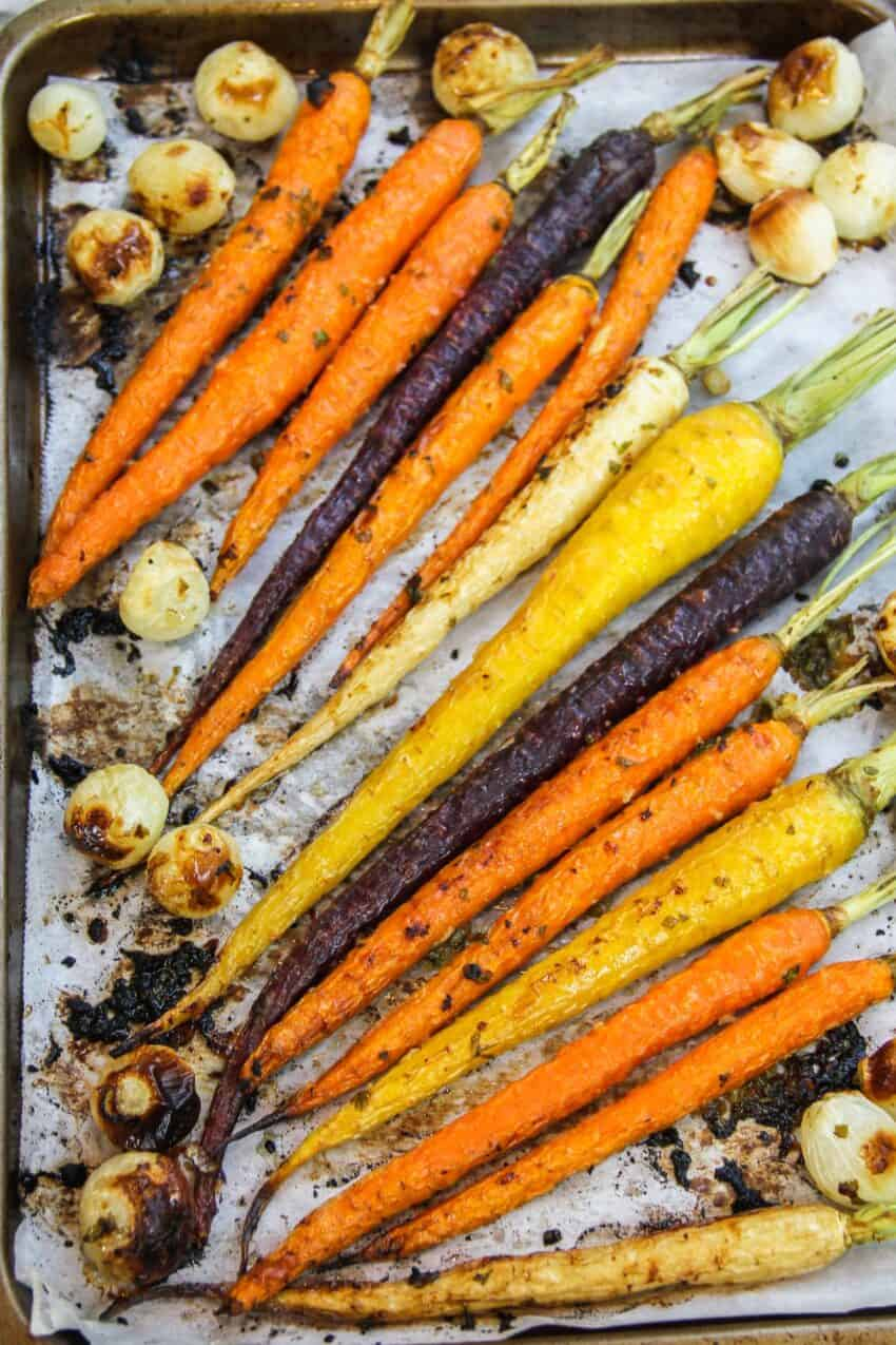 roasted carrots and pearl onions on parchment paper