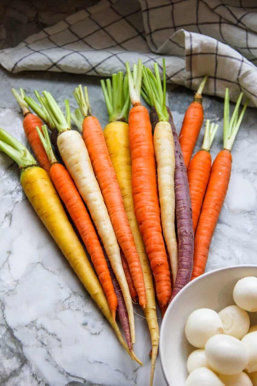 fresh carrots and pearl onions in bowl