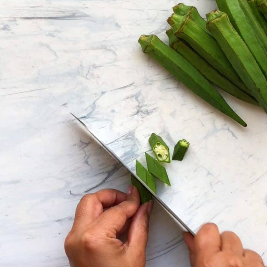 slicing okra on a white cutting board